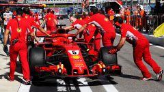 F1: meccanici Ferrari attorno alla monoposto di Sebastian Vettel