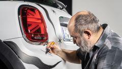 Giuseppe Palumbo impegnato a disegnare sul paraurti posteriore di Mini