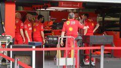I meccanici Ferrari discutono all'interno del box