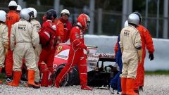Kimi Raikkonen guarda la sua Ferrari sconsolato dopo l'incidente nei test di Catalunya
