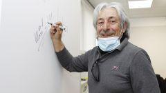 Marco Lucchinelli appone la firma sul muro del centro stile Suzuki