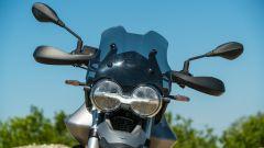 Moto Guzzi V85 TT: il dettaglio del faro anteriore con il logo dell'aquila
