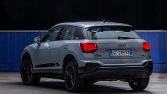 Nuova Audi Q2: una vista di 3/4 posteriore con i fari a LED accesi