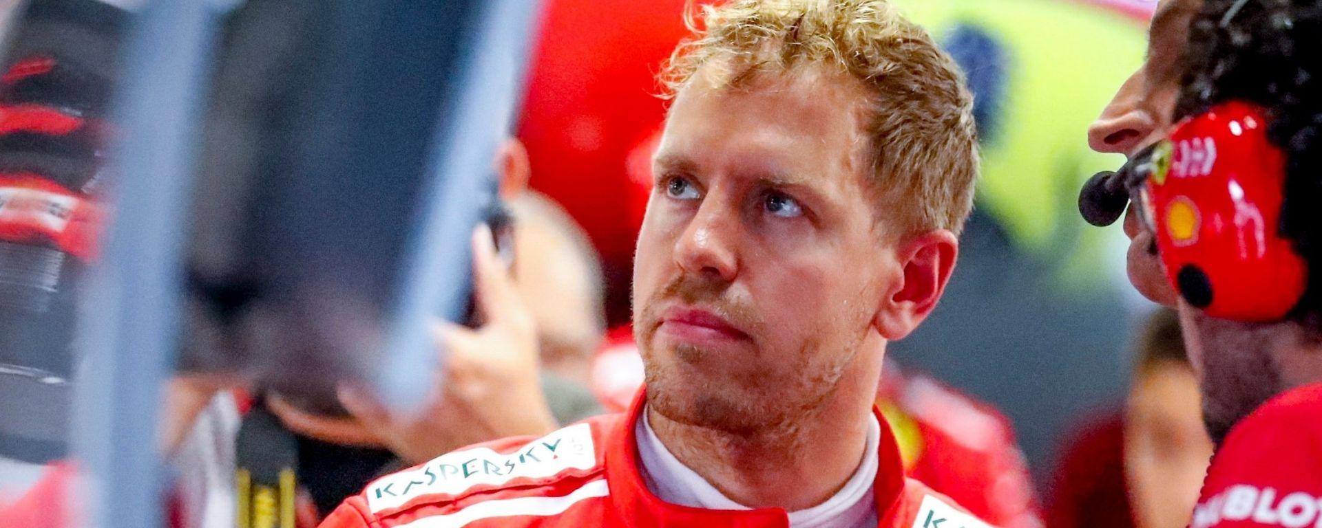 Sebastian Vettel scruta un monitor nei box della Ferrari
