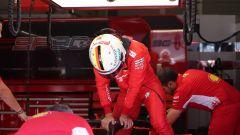 Sebastian Vettel si appoggia alla sua Ferrari mentre esce dalla monoposto