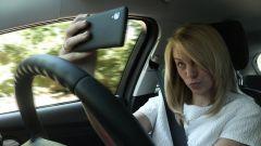 Selfie alla guida, rischio multa se si pubblica su Facebook o altri social