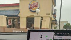 Un cliente Tesla fermatosi davanti a un ristorante della catena Burger King