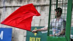 Un commissario sventola una bandiera rossa in Formula 1